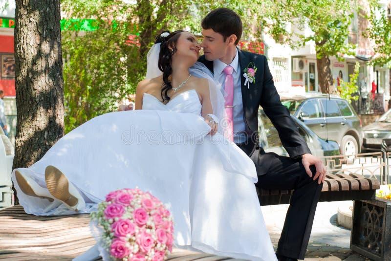 pares Novo-casados em um banco no parque imagem de stock