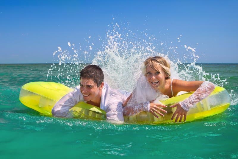 pares Novo-casados que apreciam em um colchão inflável fotos de stock royalty free