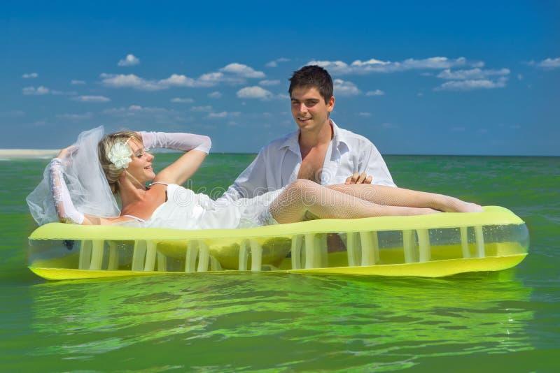 pares Novo-casados que apreciam em um colchão inflável foto de stock