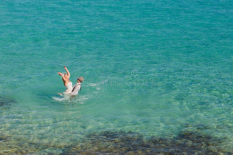 Pares novo-casados românticos que apreciam umas férias de verão Os jovens preparam o levantamento de sua noiva no mar imagem de stock royalty free