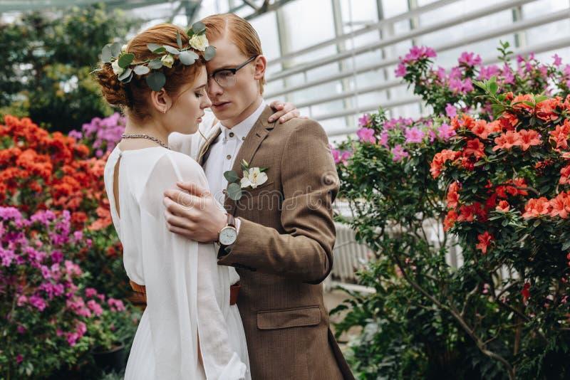 pares novos à moda do casamento do ruivo que abraçam entre flores imagem de stock royalty free