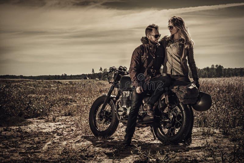 Pares novos, à moda do piloto do café em motocicletas feitas sob encomenda do vintage no campo imagem de stock royalty free