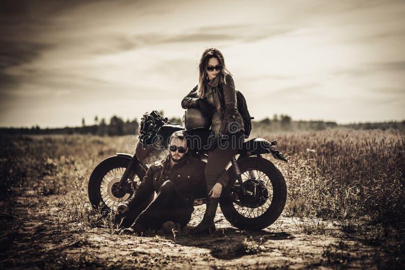 Pares novos, à moda do piloto do café em motocicletas feitas sob encomenda do vintage no campo imagem de stock