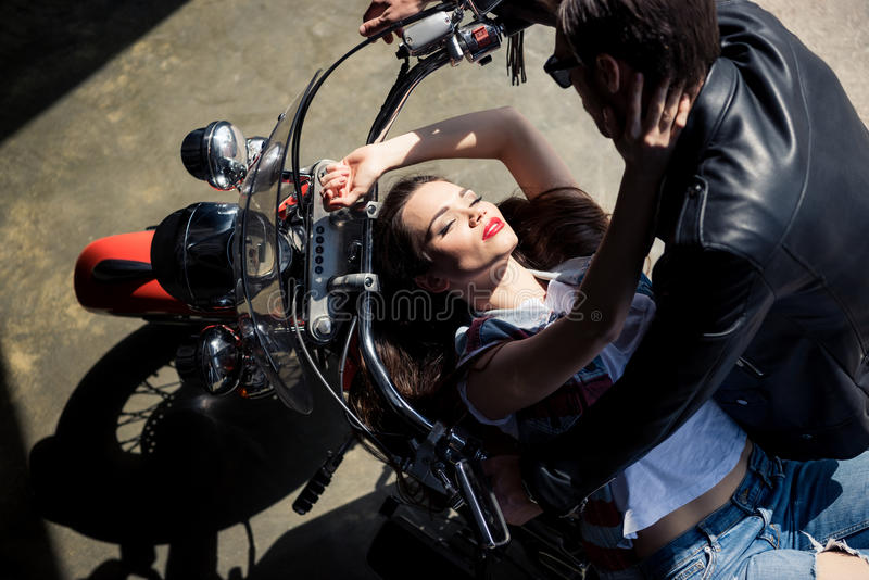 Pares novos à moda no amor que passa o tempo junto na motocicleta foto de stock
