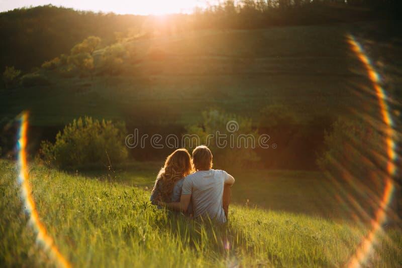 Pares novos à moda que sentam-se em um monte e que admiram o por do sol Uma foto do filme com uma luz e uma luz solar, sem uma ca imagens de stock
