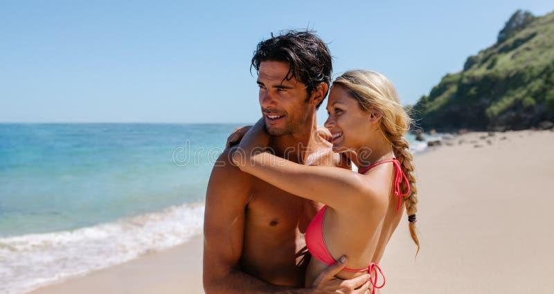 Pares novos afetuosos que abraçam na praia foto de stock