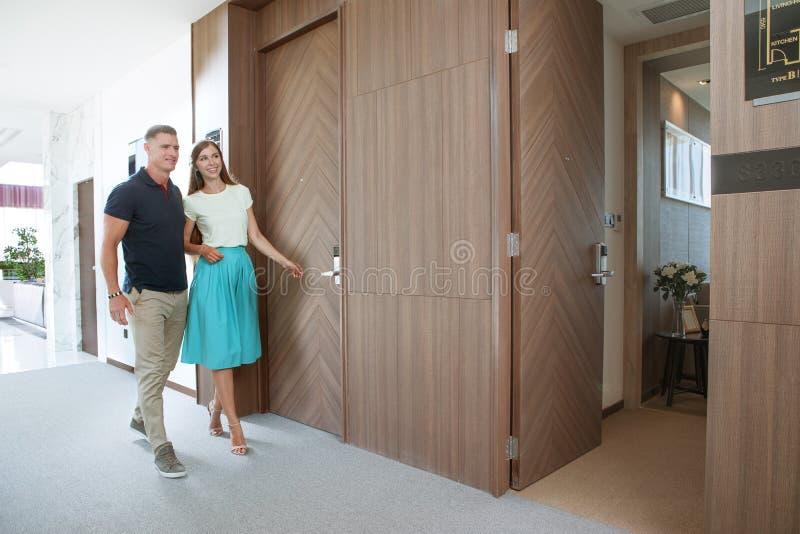 pares novos agradáveis no ambiente da casa do condomínio fotografia de stock