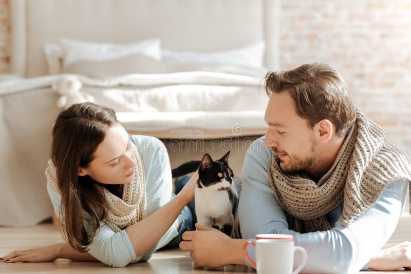 Pares novos agradáveis que jogam com o animal de estimação em casa imagens de stock