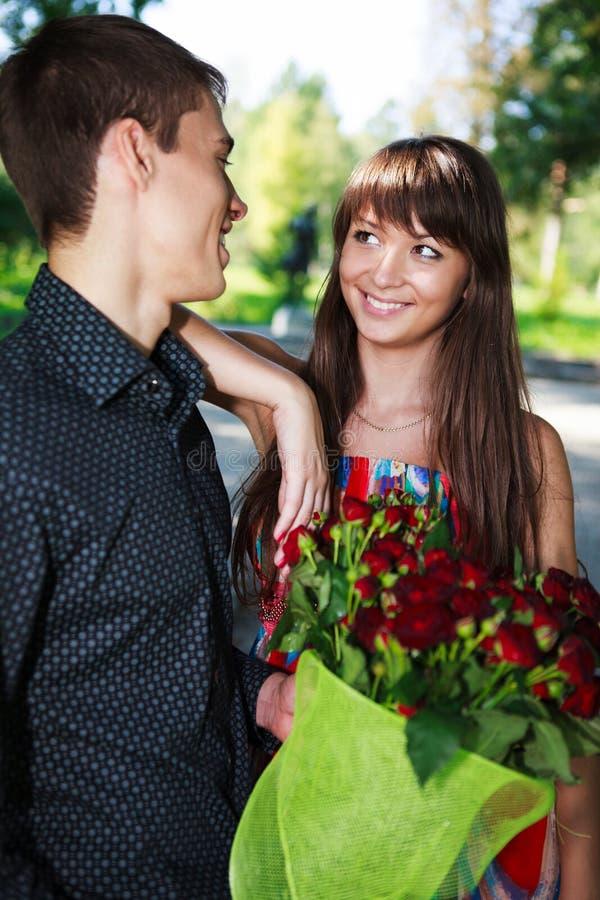 Pares novos alegres do retrato com um ramalhete de rosas vermelhas foto de stock royalty free