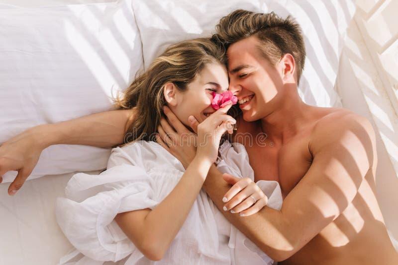 Pares novos alegres no amor que encontra-se na cama branca, apreciando a lua de mel na manhã ensolarada Homem considerável de sor fotos de stock royalty free