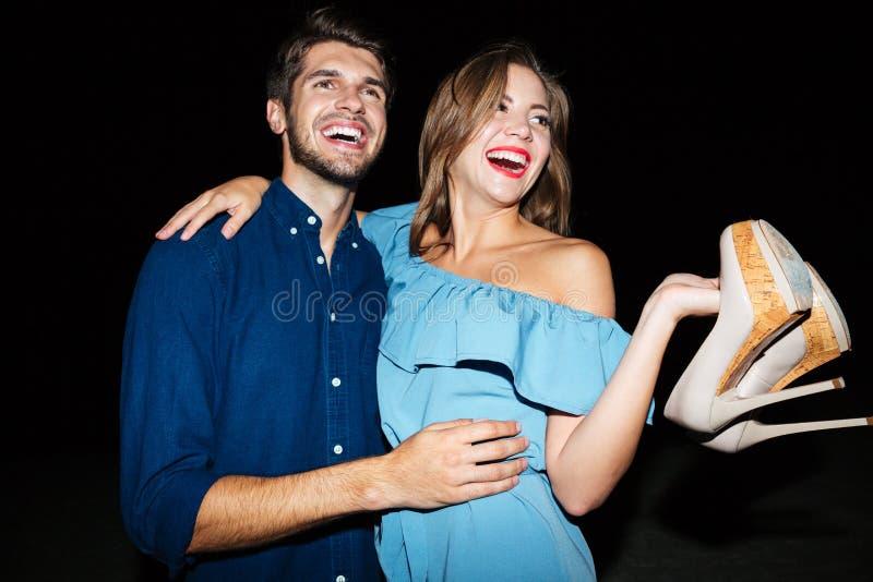 Pares novos alegres que abraçam e que têm o divertimento na noite imagens de stock