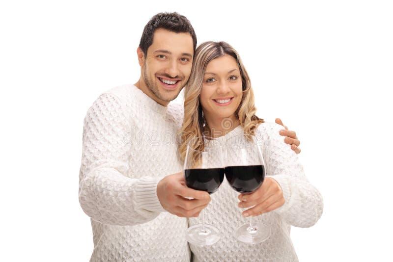 Pares novos alegres que fazem um brinde com vidros do vinho foto de stock