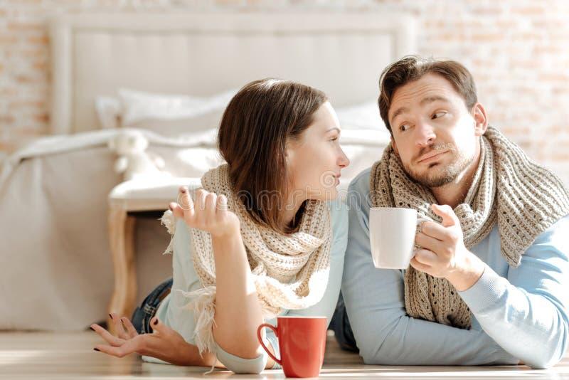 Pares novos amigáveis que comunicam-se em casa foto de stock royalty free