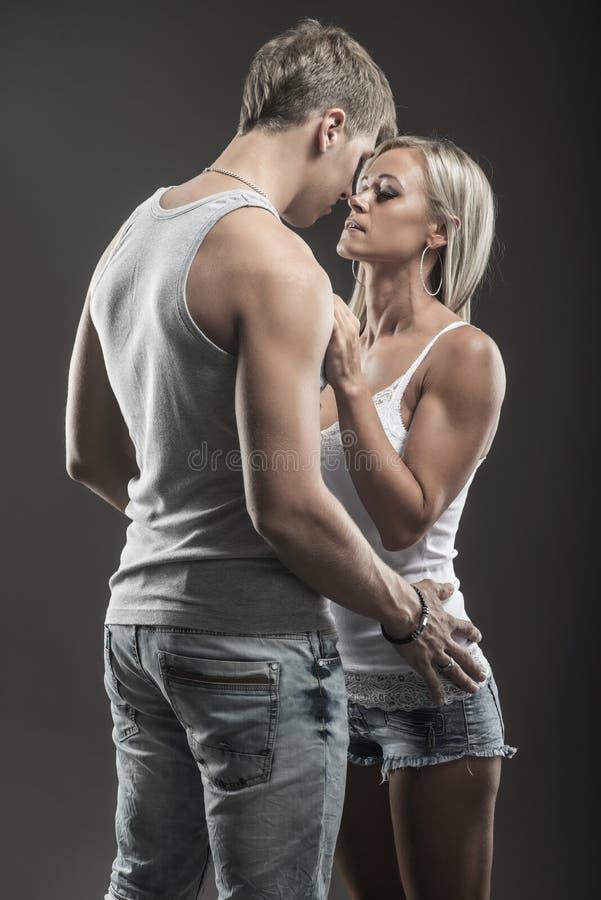 Pares novos apaixonado no amor na obscuridade fotografia de stock