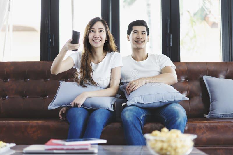 Pares novos asiáticos felizes que amam no sofá que olha um filme junto fotografia de stock