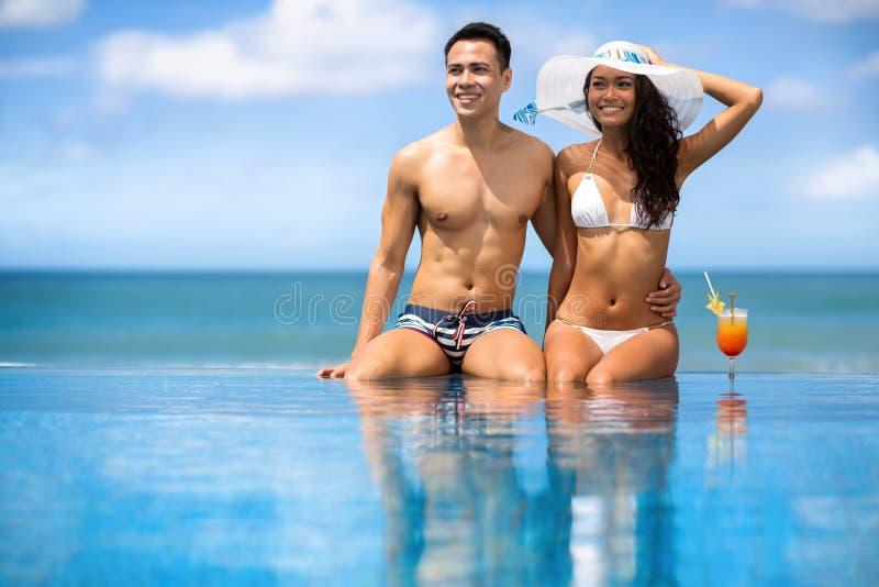 Pares novos asiáticos que sentam-se na piscina sob o verão ensolarado foto de stock royalty free