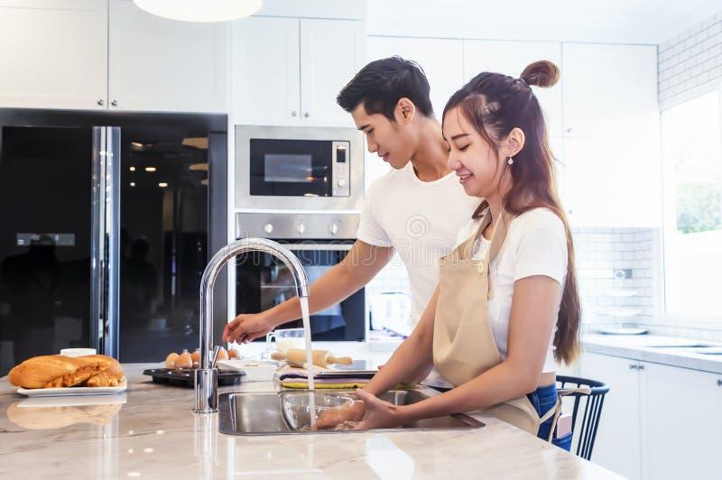 Pares novos asi?ticos bonitos que ajudam a cozinhar o bekery na cozinha em casa fotografia de stock royalty free