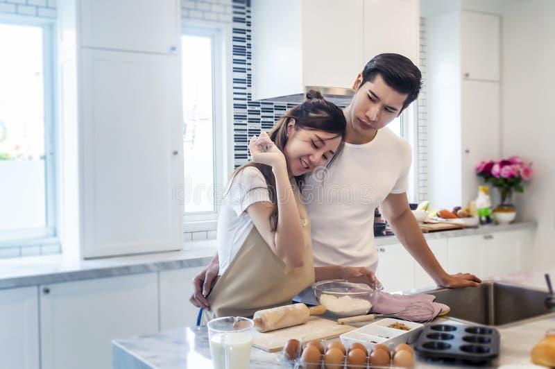 Pares novos asi?ticos bonitos que ajudam a cozinhar o bekery na cozinha em casa imagem de stock