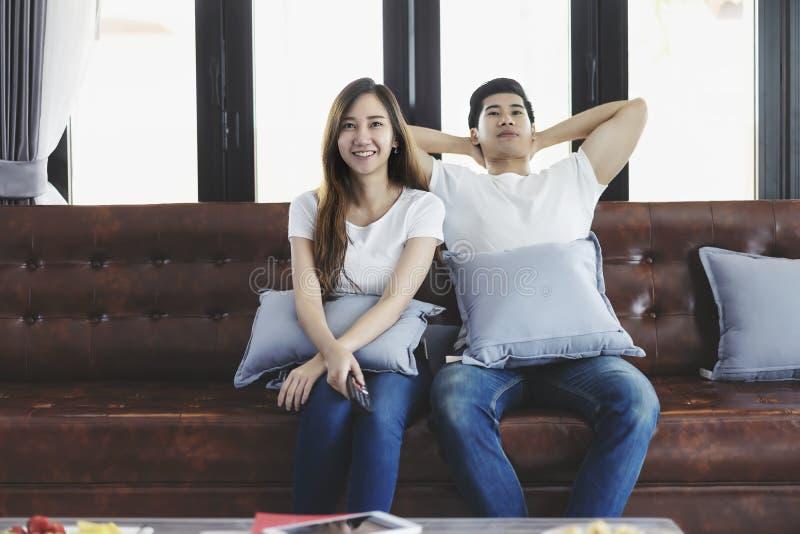 Pares novos asi?ticos felizes que amam no sof? que olha um filme junto foto de stock