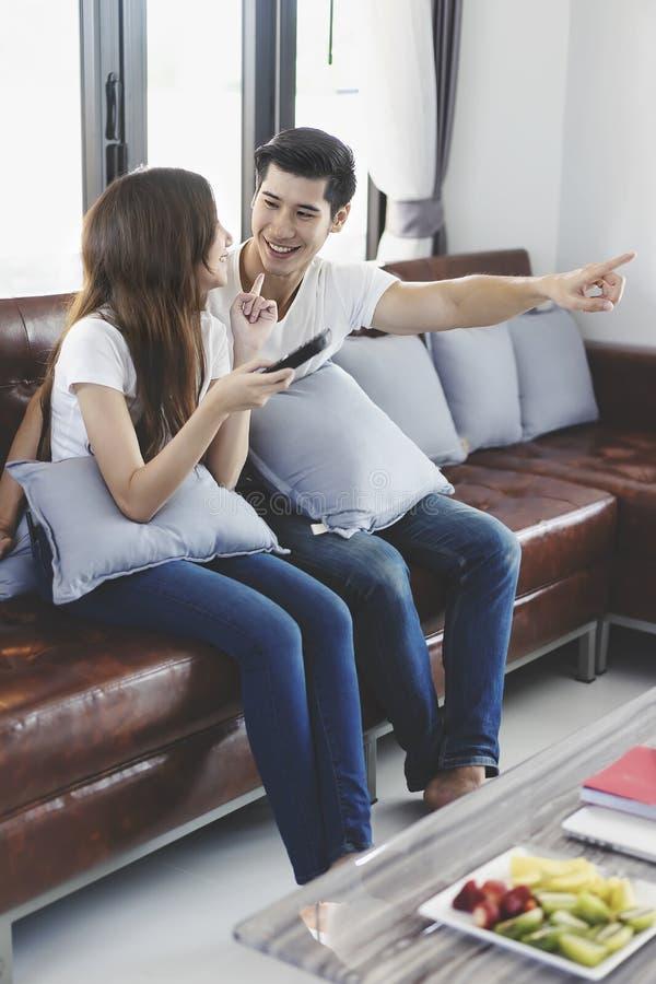 Pares novos asi?ticos felizes que amam no sof? que olha um filme junto fotos de stock