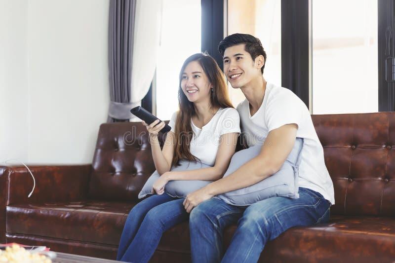 Pares novos asi?ticos felizes que amam no sof? que olha um filme junto imagens de stock royalty free