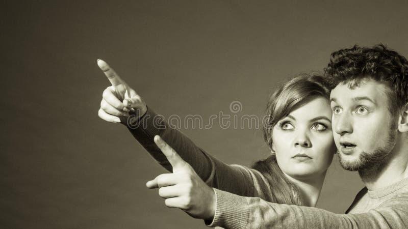 Pares novos assustado que mostram o espaço da cópia foto de stock