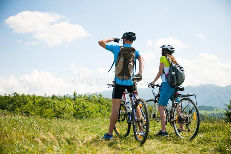 Pares novos ATIVOS que biking em uma estrada de floresta na montanha em um spr imagem de stock royalty free