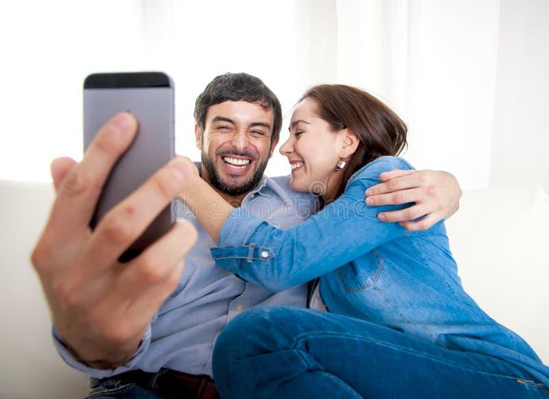 Pares novos atrativos agradáveis que sentam-se junto no sofá do sofá que toma a foto do selfie com telefone celular fotografia de stock royalty free