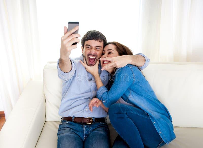 Pares novos atrativos agradáveis que sentam-se junto no sofá do sofá que toma a foto do selfie com telefone celular foto de stock royalty free