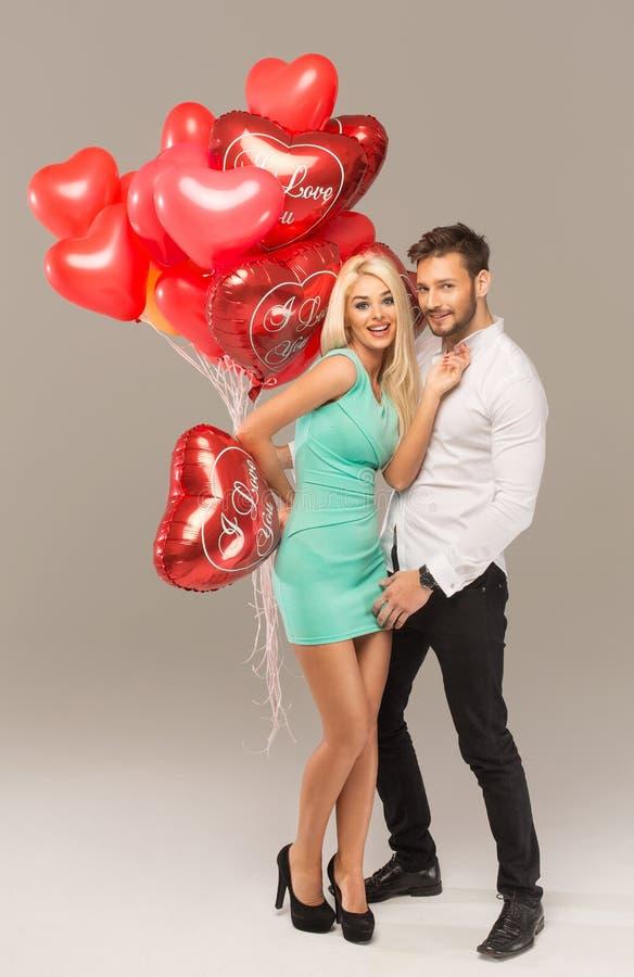 Pares novos atrativos com balões do coração fotos de stock royalty free