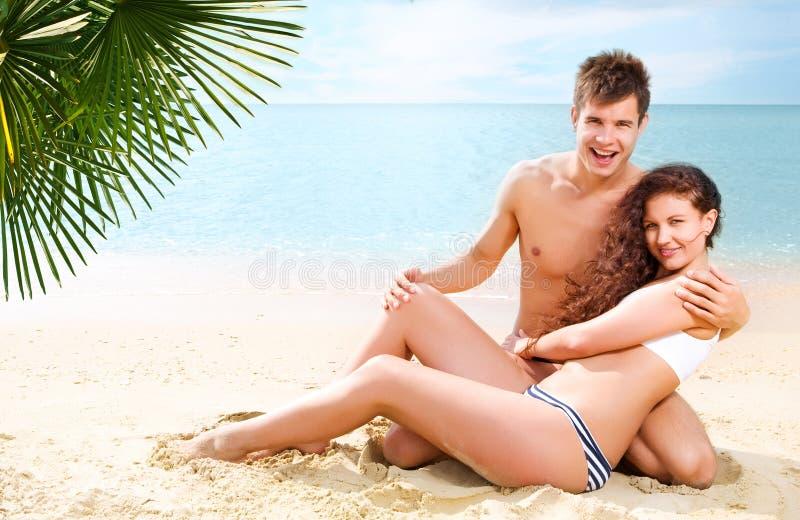 Pares novos atrativos na praia imagem de stock royalty free