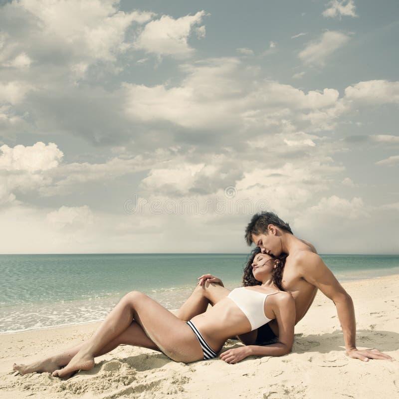 Pares novos atrativos na praia fotografia de stock royalty free