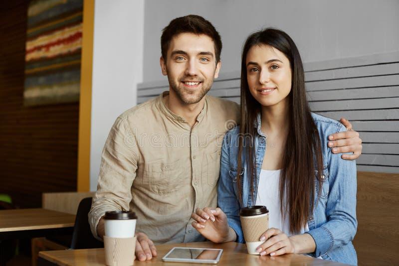 Pares novos bonitos com cabelo escuro em sorrisos da roupa ocasional, no café bebendo e no levantamento para a foto no artigo da  fotografia de stock