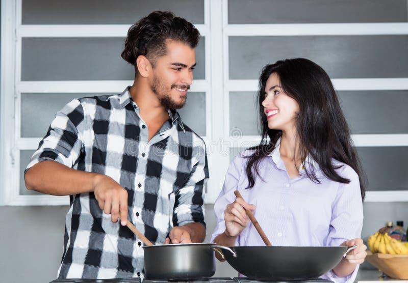 Pares novos bonitos do amor que cozinham na cozinha imagens de stock