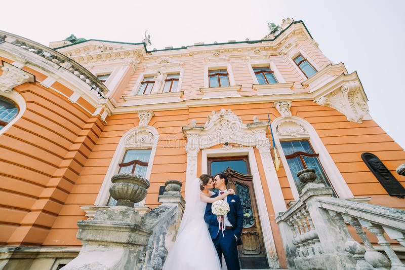 Pares novos bonitos do casamento em escadas do palácio antigo romântico imagem de stock royalty free
