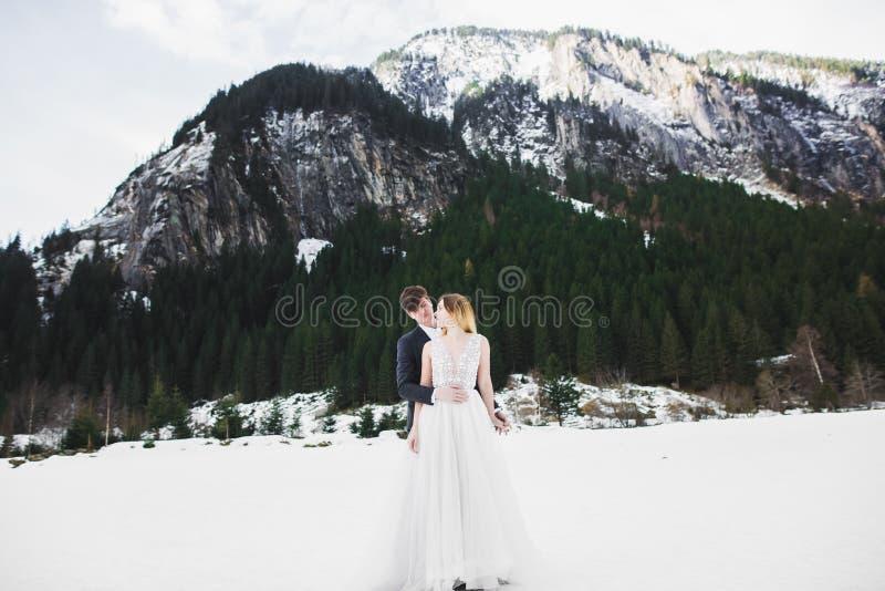 Pares novos bonitos em montanhas do inverno Caminhada do inverno dos amantes Homem que abraça a mulher fotografia de stock royalty free