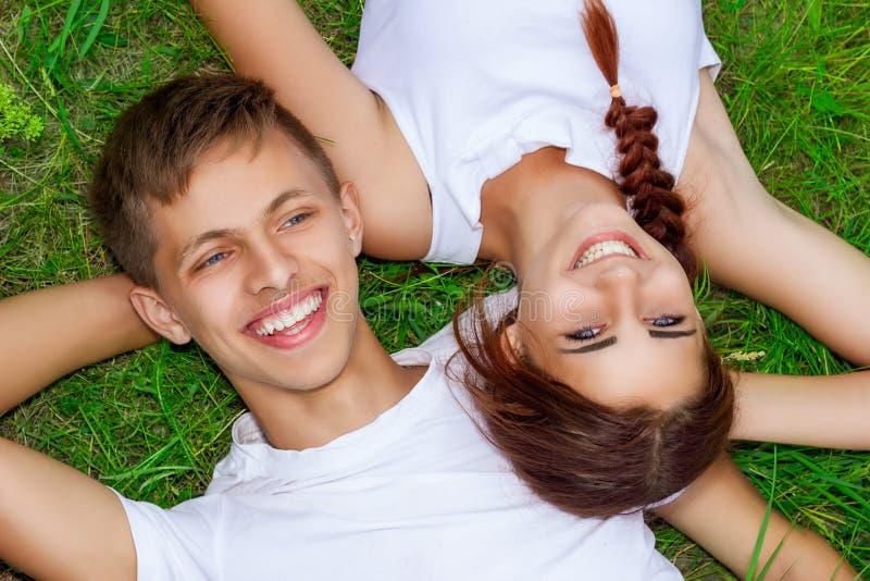 Pares novos bonitos na grama verde com sorriso na cara, relacionamento feliz foto de stock