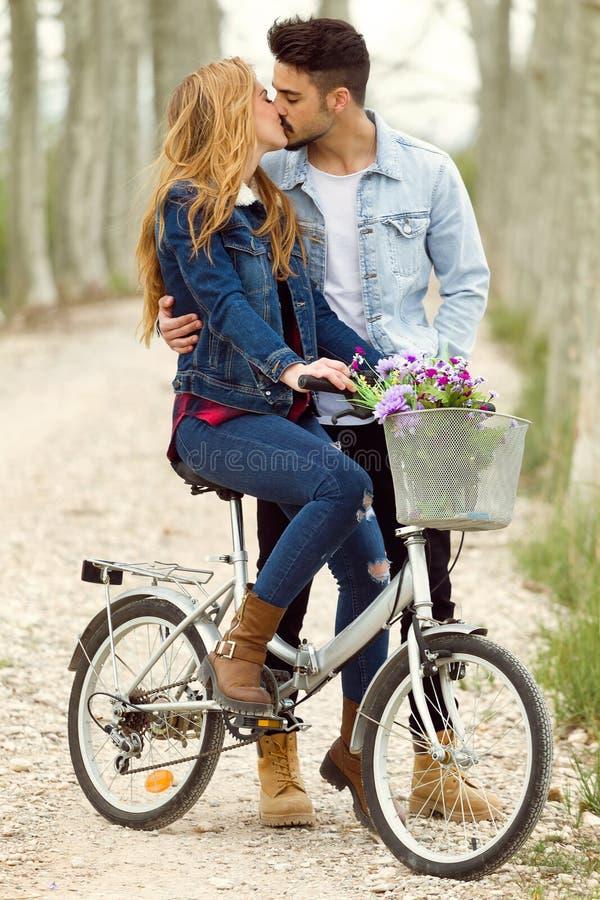 Pares novos bonitos no amor na bicicleta no parque imagem de stock royalty free