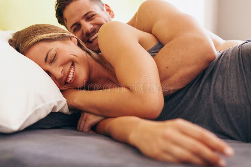 Pares novos bonitos no amor que encontra-se na cama foto de stock