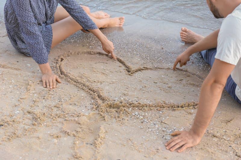 Pares novos bonitos perto do coração tirado na areia da praia imagens de stock
