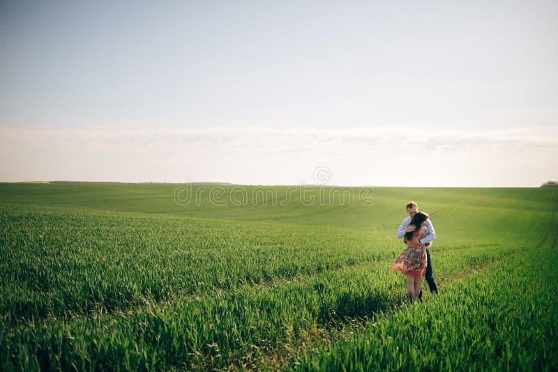Pares novos bonitos que abraçam delicadamente na luz do sol no campo do verde da mola Família feliz que abraça no prado verde com foto de stock