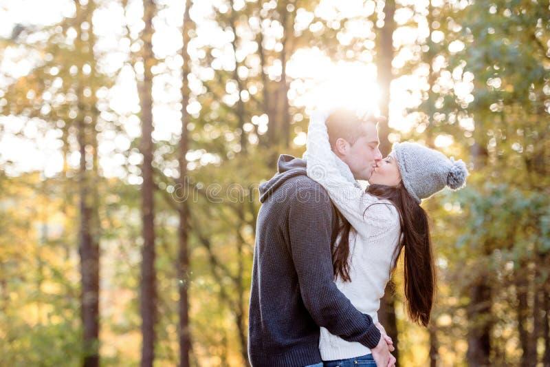 Pares novos bonitos que abraçam e que beijam Natureza ensolarada do outono fotos de stock