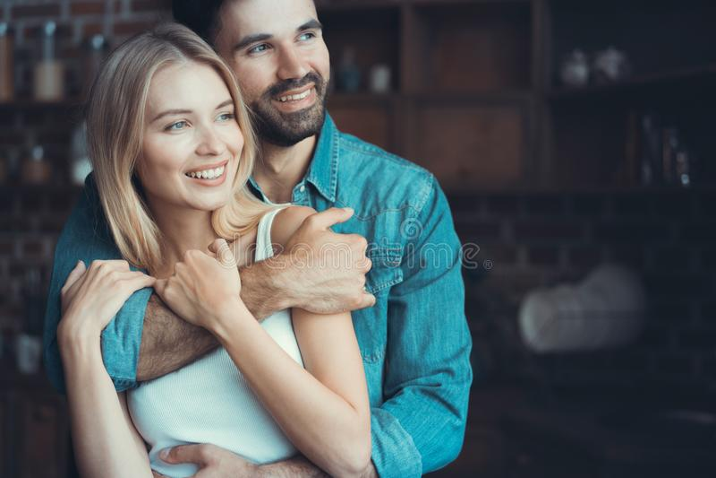 Pares novos bonitos que abraçam em seu apartamento novo fotos de stock royalty free