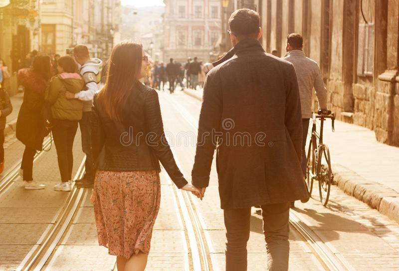 Pares novos bonitos que andam abaixo da rua ensolarada foto de stock royalty free