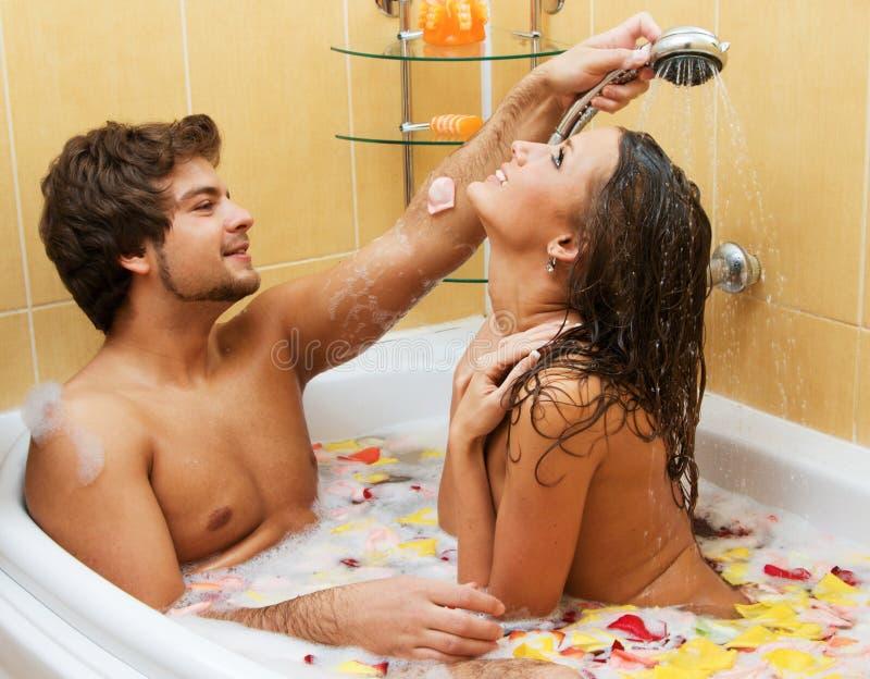 Pares novos bonitos que apreciam um banho imagens de stock royalty free