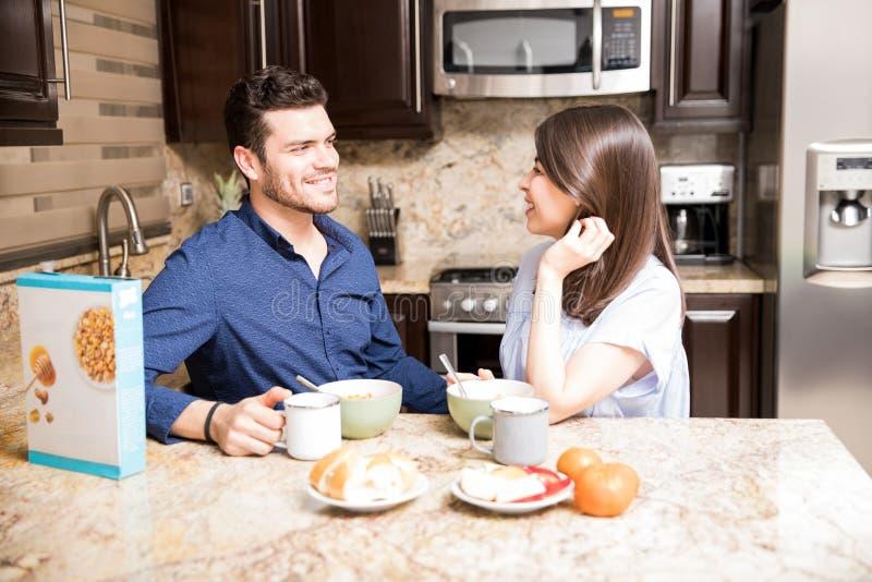 Pares novos bonitos que comem o café da manhã na cozinha fotografia de stock