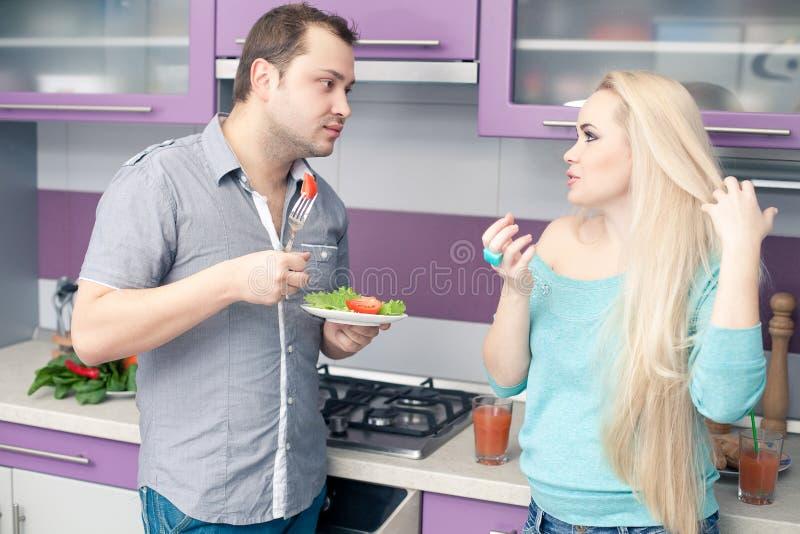 Pares novos bonitos que comem a salada do legume fresco fotos de stock