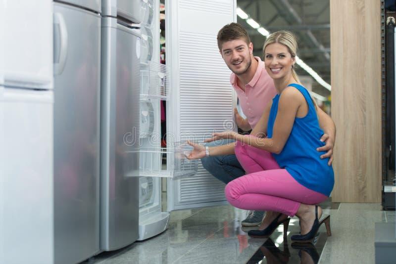 Pares novos bonitos que compram um refrigerador no supermercado fotografia de stock royalty free
