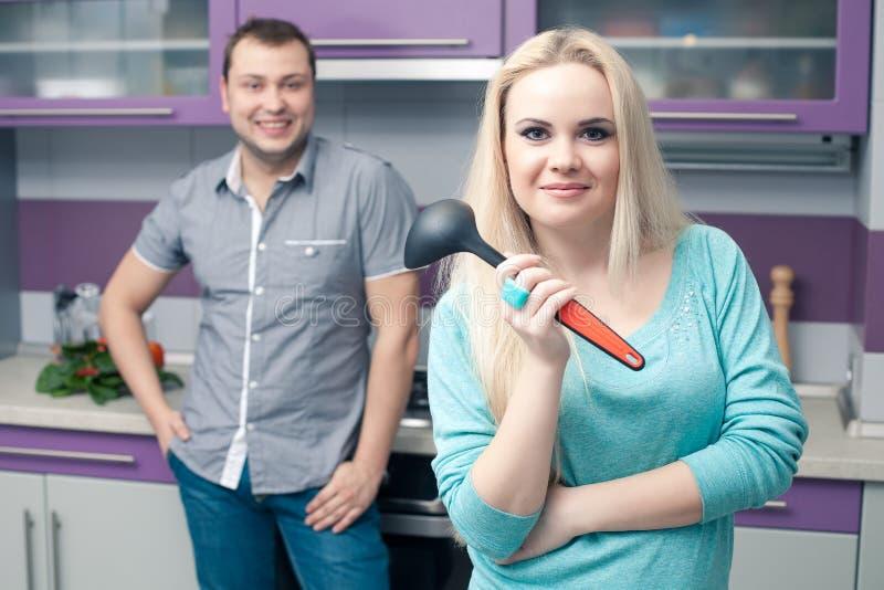 Pares novos bonitos que estão em sua cozinha foto de stock