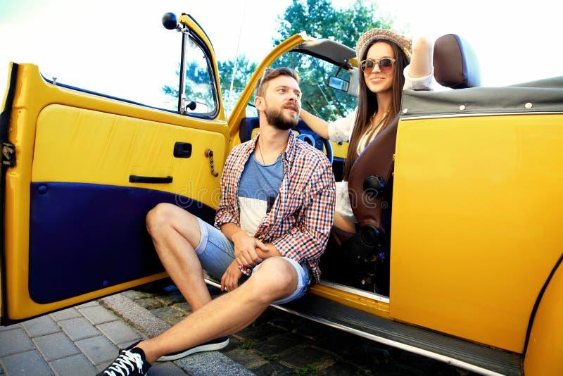Pares novos bonitos que falam e que sorriem ao estar perto de seu convertible novo imagens de stock